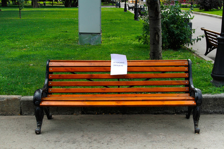 A freshly painted bench in the park with a caution sign  (translated from the Russian Caution. Wet paint)