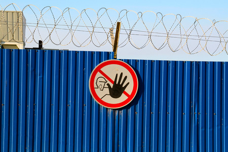 intruder: Sign No access for unauthorised persons on blue fence with barbed wire Stock Photo