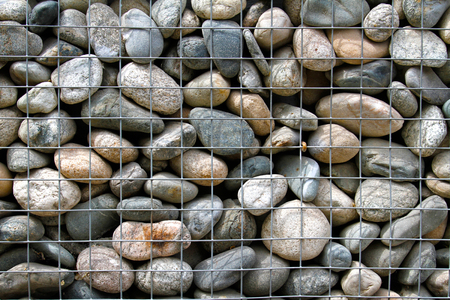gabion mesh: Stone wall in metal cage as background or texture