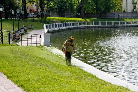 off cuts: Kaliningrad, Russia - August 3, 2016: The worker of a garden cuts off a grass near the pond in Kalinigrad