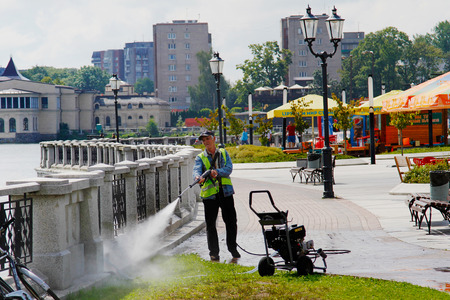 Kaliningrad, Russia - August 3, 2016: The worker is cleaning fence with high pressure water cleaner