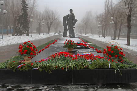 assigned: Volgograd, Russia - February 03, 2013: Red carnations assigned to the monument to Komsomol members in Volgograd. Event dedicated to the celebration of Victory Day in the battle of Stalingrad. Authors: sculptor A.Y. Krivolapov and architect V.P. Kalinichen Editorial