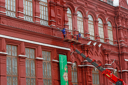 Moscow, Russia - July 07, 2015: Workers with water hose wash Moscow historical museum building in the Red Square in Moscow Editorial