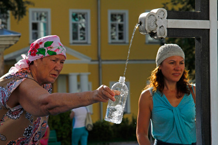 Sergiev Posad, Moscow Region, Russia - August 11, 2015: People collect the holy water in bottle in the Trinity Sergius Lavra in Sergiev Posad