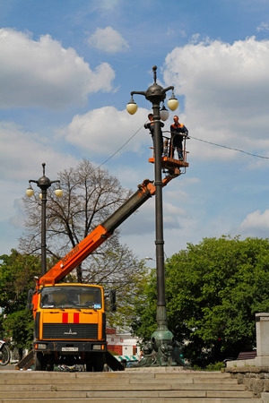 Moscow, Russia - June 14, 2016: Electricians in bucket at height repair a streetlight in Moscow