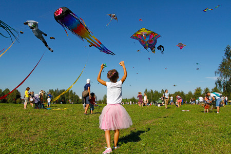 Moscow, Russia - August 27, 2016: Girl launches a kite into the sky at the kite festival in the Park Tsaritsyno in Moscow