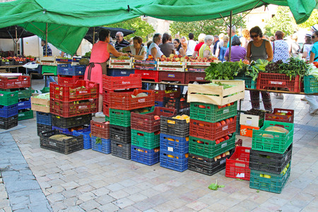 Besalu, Spain - September 09, 2014: Sale of fruit and vegetables in street of Besalu in Spain. Fruit and vegetables in plastic and wooden boxes at farm market.