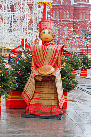 Moscow, Russia - February 21, 2017: Russian Shrovetide statue in traditional colorful dress with a loaf at Russian national festival Shrove in Moscow Editorial