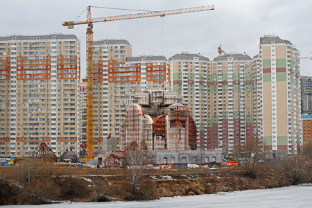 Moscow, Russia - March 15, 2017: Nikolskaya church under construction on the background of residential buildings in Moscow