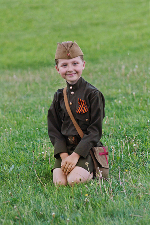 enfermera con cofia: Volgograd, Russia - May 9, 2012: A little girl in a military uniform sitting on the grass on Victory Day celebration in Volgograd Editorial