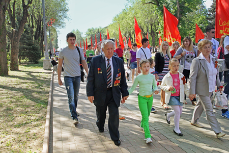 accompanied: Volgograd, Russia - May 9, 2013: World War II veteran accompanied by relatives on Victory Day celebration in Volgograd