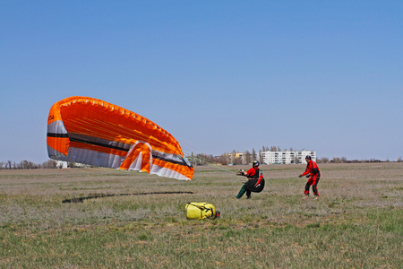 Volgograd, Russia - April 20, 2013: Assistant helps the paraglider to straighten the paraplane before the flight in Volgograd