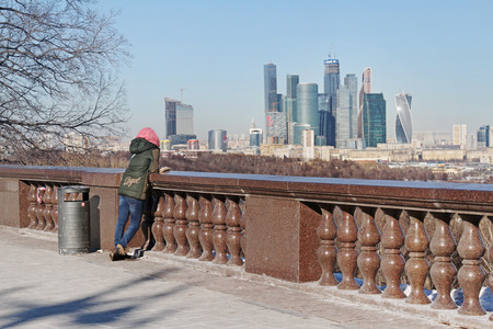 Moscow, Russia - February 17, 2015: Woman stands on observation deck of the Vorobyovy Gory and watching to the business center