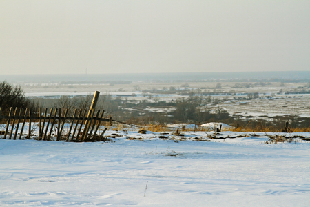 rickety: Old rickety fence against the background of a winter field in the horizon