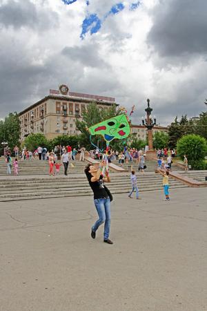 Volgograd, Russia - June 12, 2014: Smiling woman launches a kite into the sky at the kite festival in Volgograd Editorial