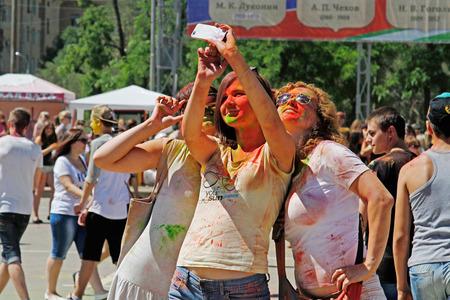 Volgograd, Russia - June 14, 2015: Portrait of young happy girls making selfie on Holi color festival in Volgograd