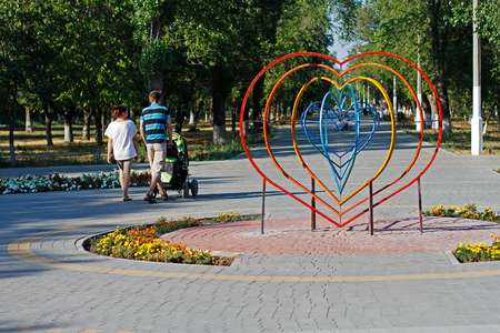 sidewalk talk: Volgograd, Russia - July 26, 2015: Young parents are walking next to an installation in the form of a heart in the park in Volgograd Editorial