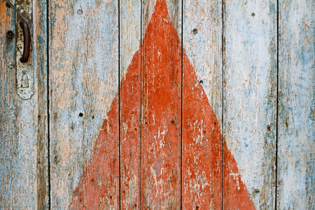 Painted red triangle on the old wooden door with handle as background or texture