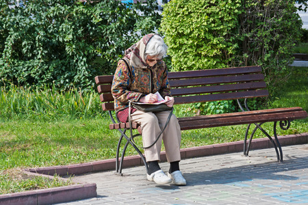 Volgograd, Russia - September 11, 2011: Old woman sits on the bench and unravels a crossword puzzle in the park in Volgograd