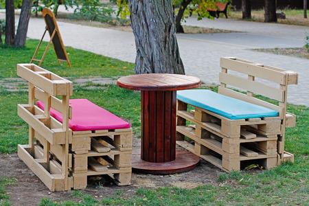 Wooden bench made of pallets for sitting with table made from coil of electric cable outdoors