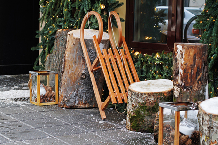 Wooden sled with stumps and glass candlesticks as christmas decoration near a cafe