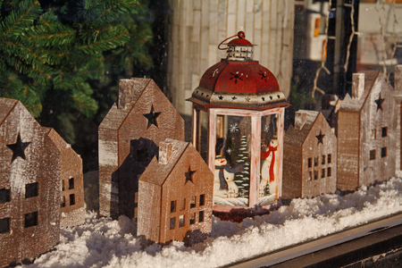Wooden toy houses and christmas candlestick on store showcase