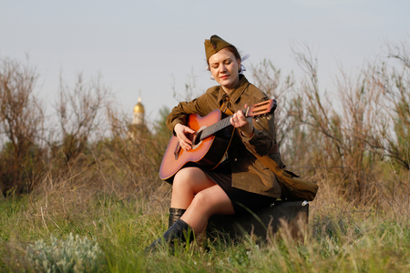 Pretty Soviet female soldier in uniform of World War II plays the guitar