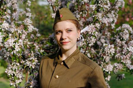 Pretty Soviet female soldier in uniform of World War II stands near flowering tree