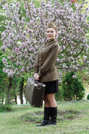Pretty Soviet female soldier in uniform of World War II with suitcase stands on a stump near flowering tree