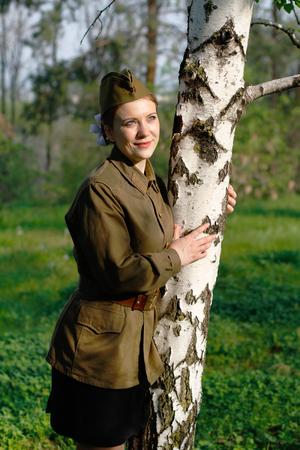Pretty Soviet female soldier in uniform of World War II stands near the birch