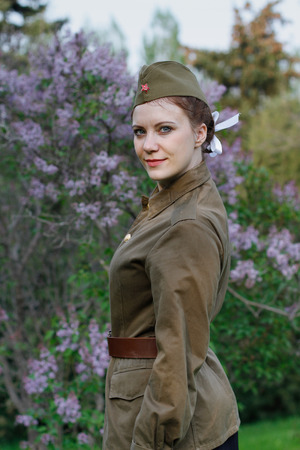 Pretty Soviet female soldier in the form of the Second World war against the background of lilac Stock Photo