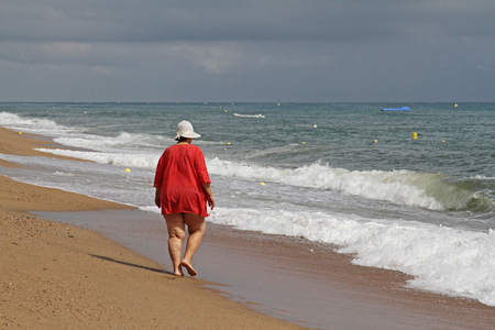 Back view of a fat woman walking alone on a sunny day on the beach of the Mediterranean Sea in Calella 版權商用圖片