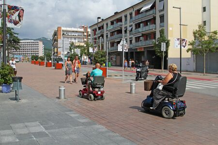Calella, Spain - September 08, 2014: People on electric wheelchairs ride down the street in Calella