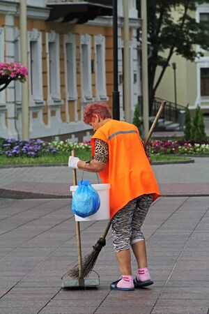 Grodno, Belarus - August 12, 2013: Street female cleaner sweeping the street in Grodno