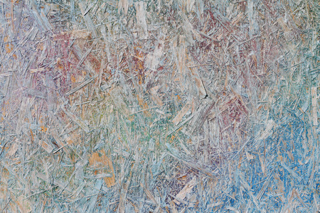 Colorful (green, blue, violet and yellow) painted OSB board as background, texture