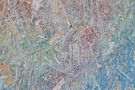 Colorful (blue, violet, green and yellow) painted OSB board as background, texture Stock Photo