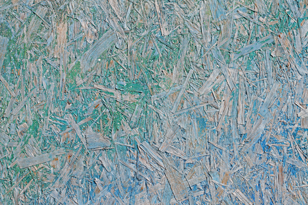 Colorful (blue, green, turquoise and yellow) painted OSB board as background, texture