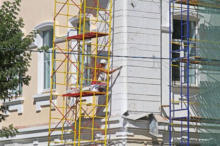 Smolensk, Russia - August 05, 2013: Builder worker painting facade of building in Smolensk