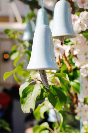 Blue ceramic bell with a tongue in the form of a feather hanging on a branch of flowering tree