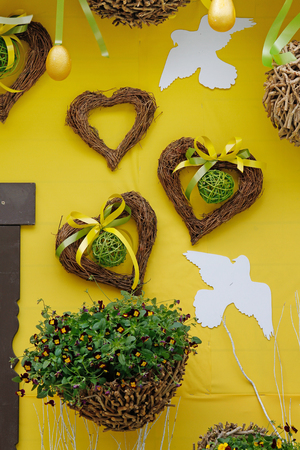 Heart shaped wreaths, birds and pansies in the basket hanging on yellow wall