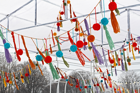Garland of colored pompons and tassels hanging at the festival.