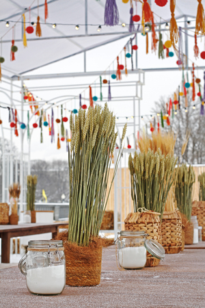 Green and dry rye in wicker pots and jars of salt standing on the table at the festival Stock Photo
