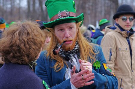 Moscow, Russia-March 24, 2018: Longhaired participant in green hat, elf ears and with smoking pipe at the St. Patricks Day Parade in the park Sokolniki in Moscow