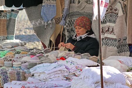 Vyborg, Russia - October 19, 2013: Woman seller sits and knits wool products for sale on the Market Square in the center of Vyborg