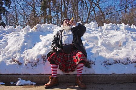 Moscow, Russia-March 24, 2018: Man in a red checkered Scottish kilt playing the horn at the St. Patricks Day Parade in the park Sokolniki in Moscow Editorial