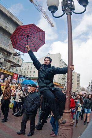 Moscow, Russia - April 10, 2011: Smiling young man with umbrella hanging on lamp post on a flashmob on Arbat in Moscow