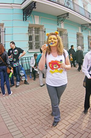 Moscow, Russia - April 22, 2012: Portrait of young woman with face painting lion and lion ears blowing soap bubbles on a flashmob on Arbat in Moscow