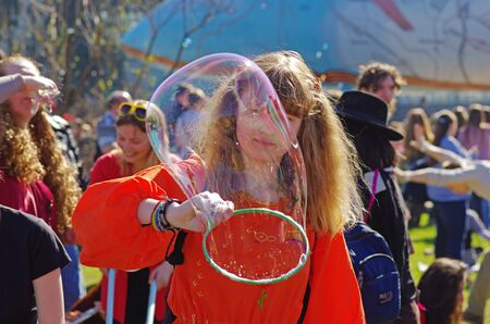 Moscow, Russia - May 02, 2013: Portrait of a girl making big soap bubble on a flashmob in VDNKh in Moscow