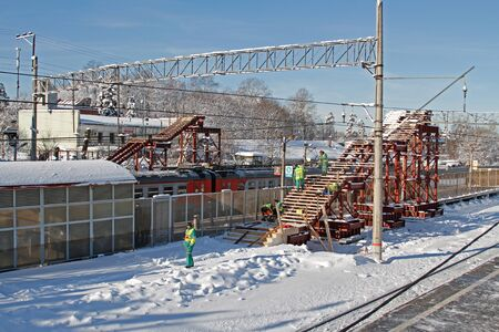 Vidnoe, Moscow region, Russia - February 14, 2019: Workers assemble a temporary overhead bridge over the railroad in Vidnoe