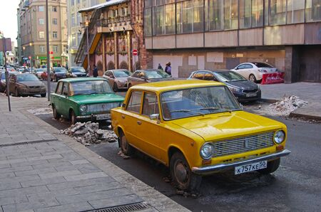 Moscow, Russia - March 17, 2018: Green and yellow soviet motor cars VAZ 2101 Zhiguli standing on the Arbat in Moscow